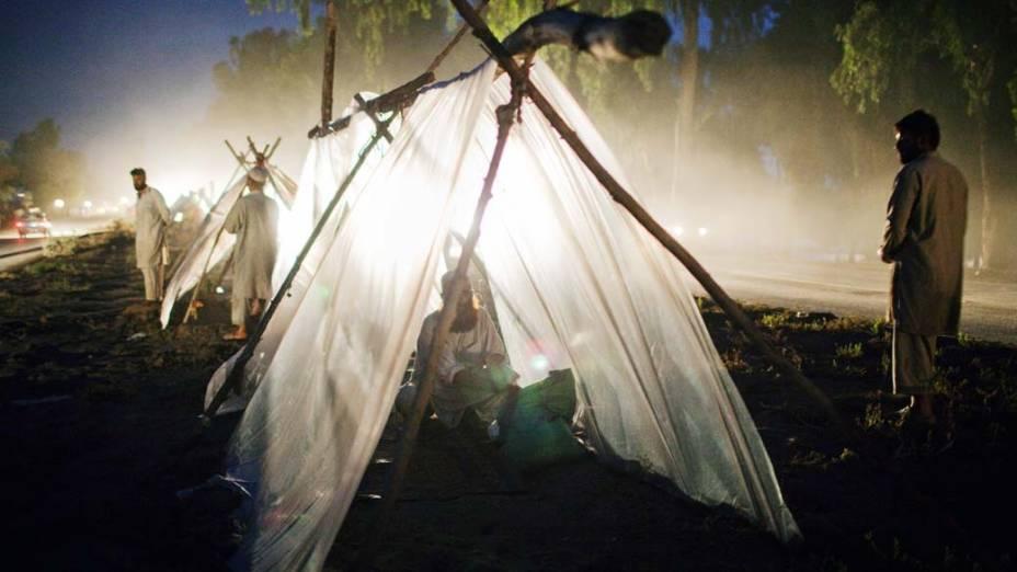 Famílias preparam-se para passar a noite em tendas improvisadas após terem abandonado seus lares, destruídos pelas enchentes no Paquistão