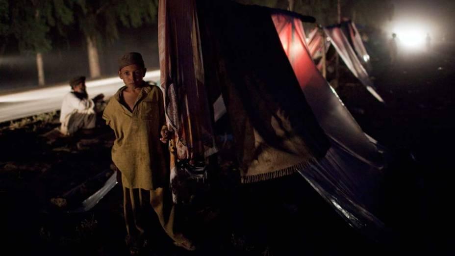 Criança recebe abrigo em tenda construída na rua para os sobreviventes das enchentes no Paquistão