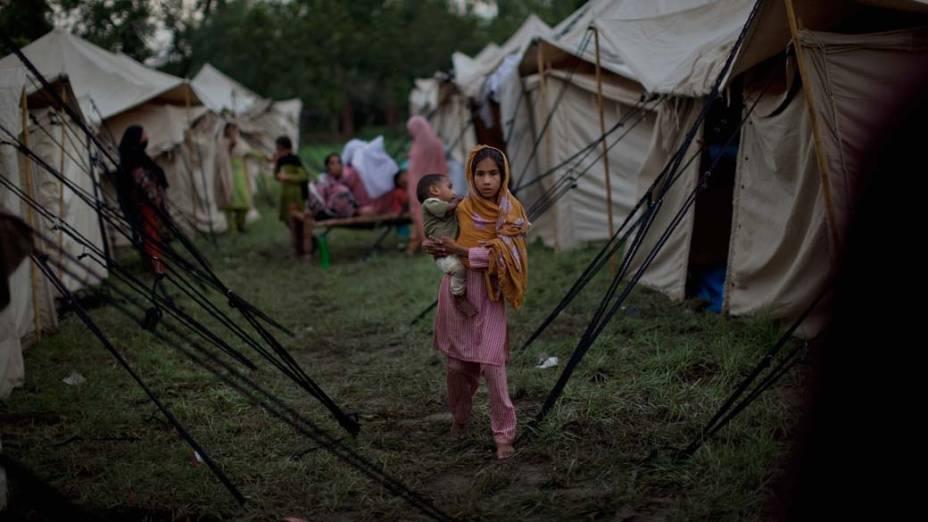 Menina segura bebê em campo de desabrigados em Nowshera, no Paquistão