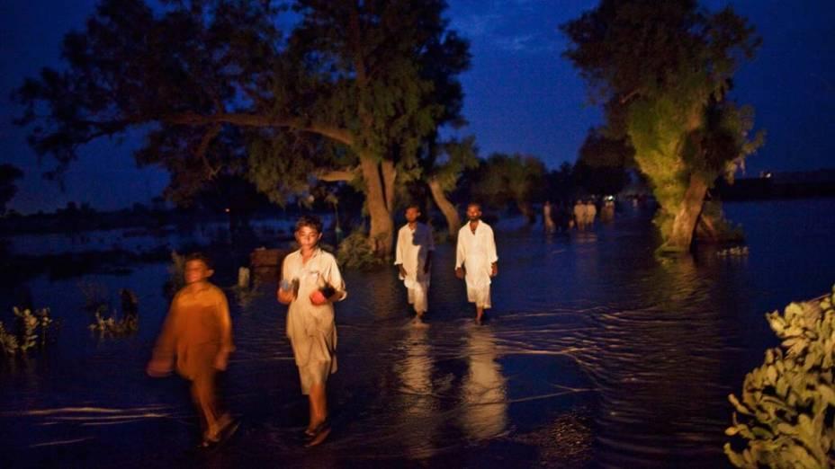 Habitantes de Nowshera, no Paquistão, caminham pelas ruas alagadas da região
