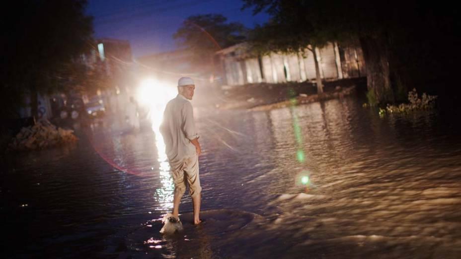 Homem caminha por rua alagada em Nowshera, no Paquistão