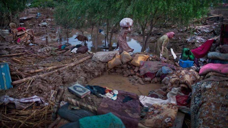 Mulheres tentam recuperar pertences entre escombros de sua casa alagada em Nowshera, no Paquistão