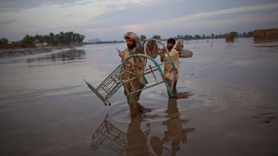 Habitantes de Nowshera, no Paquistão, carregam móveis de suas casas alagadas pelas chuvas