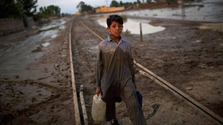 Menino carrega galões de água potável em área alagada de Nowshera, no Paquistão