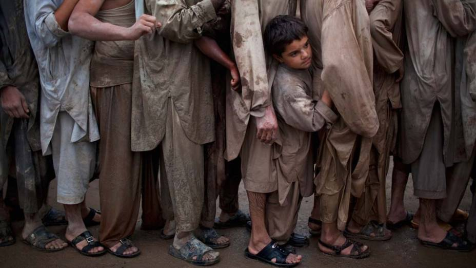 Paquistaneses fazem fila para receber mantimentos na cidade de Pabi, afetada pelas enchentes