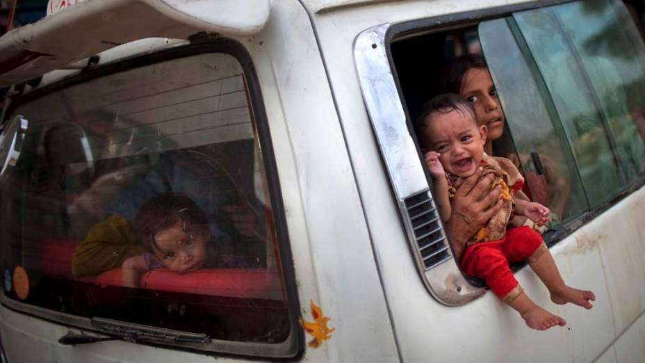 Família fica presa no trânsito ao deixar a cidade de Nowshera, no Paquistão, devido às enchentes locais
