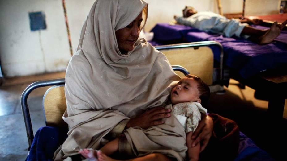 Mulher cuida de sua filha em hospital improvisado em Nowshera, no Paquistão. A criança foi infectada por um vírus que se espalhou devido às enchentes no local