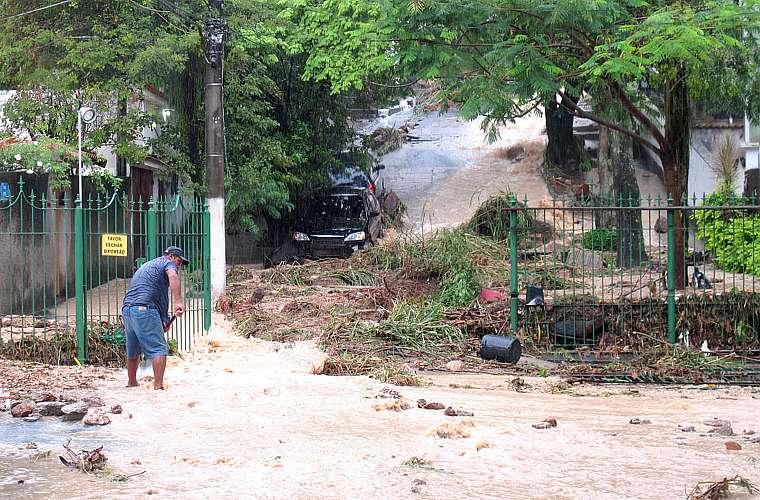 Morador tenta retirar a lama trazidas pela água da chuva na rua Tupis, no bairro São Francisco, em Niterói.