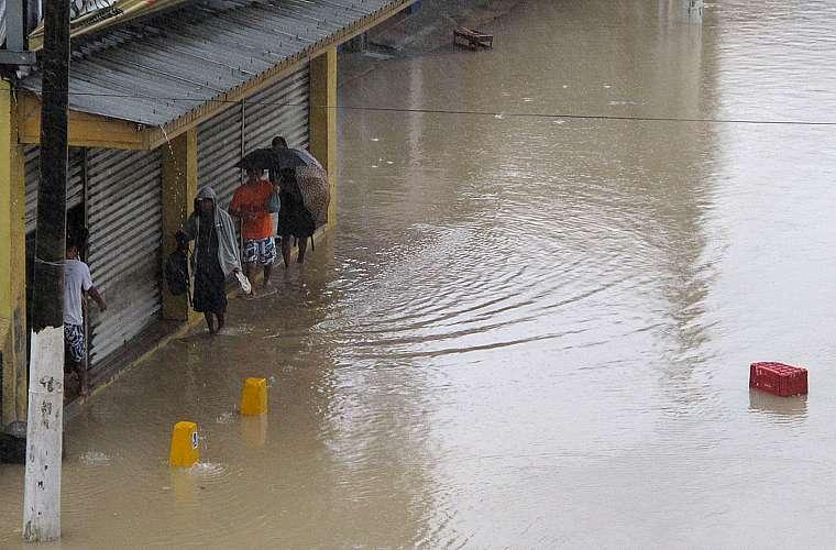 Pessoas se arriscam ao passar por um ponto de alagamento próximo à ponte Rio-Niterói.