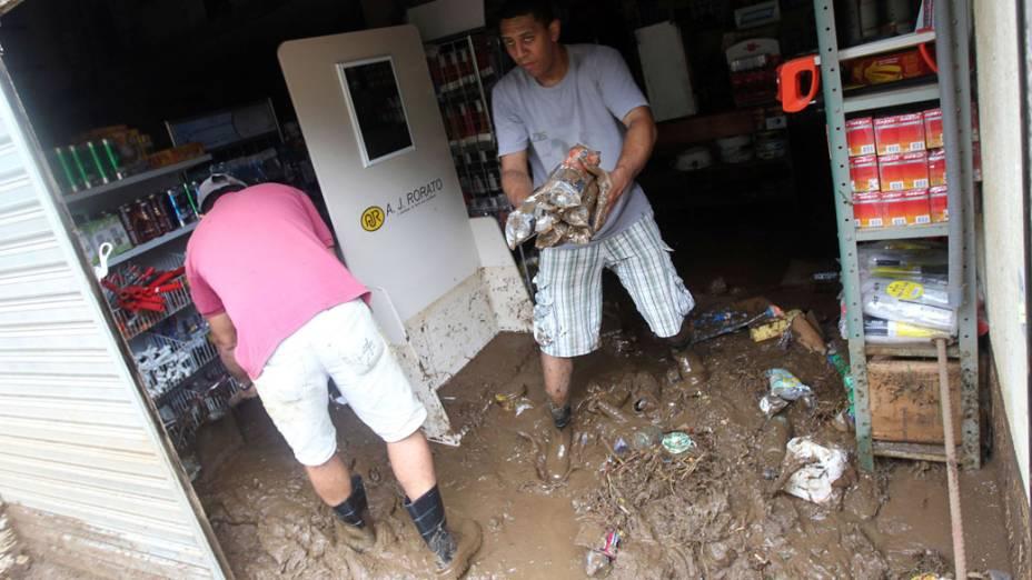 Trabalhadores limpam loja após alagamentos em Teresópolis, Rio de Janeiro - 13/01/2011