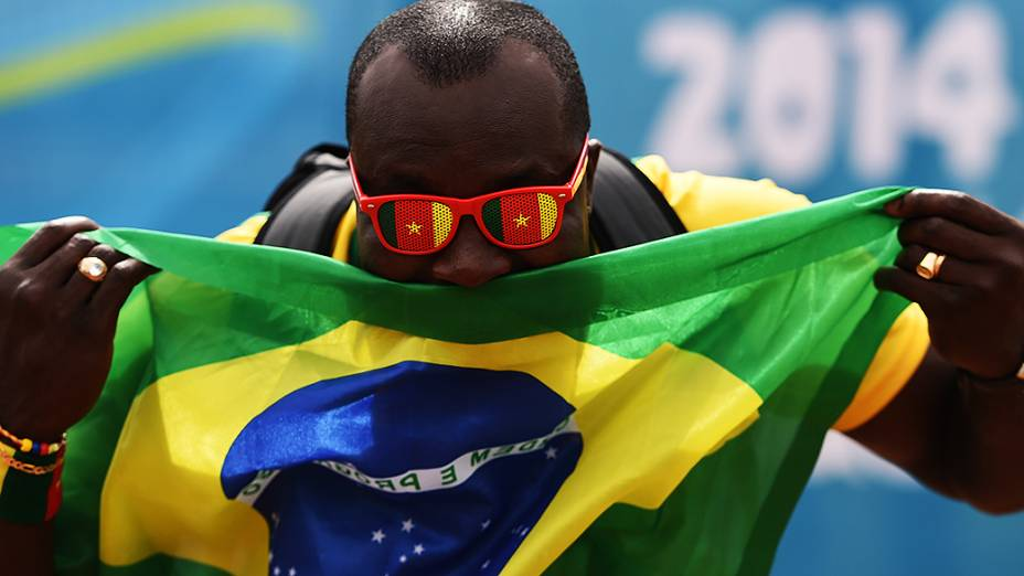 Torcedor segura a bandeira do Brasil antes do jogo contra Camarões no Mané Garrincha, em Brasília