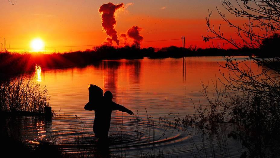 O sol nasce em Selby, no norte da Inglaterra, enquanto um homem carrega um saco de alimento para animais