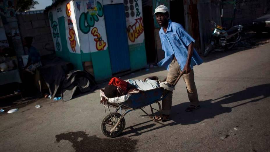 Homem carrega garoto com cólera para hospital improvisado pelos Médicos Sem Fronteiras em Porto Príncipe, Haiti