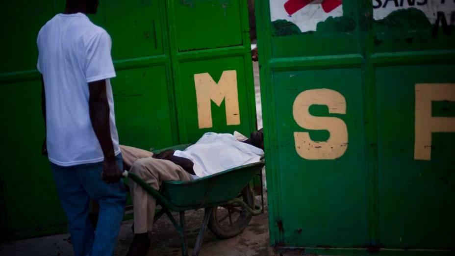 Homem carrega doente com cólera para o hospital Santa Catherine que está sendo mantido pelos Médicos Sem Fronteiras em Porto Príncipe, Haiti