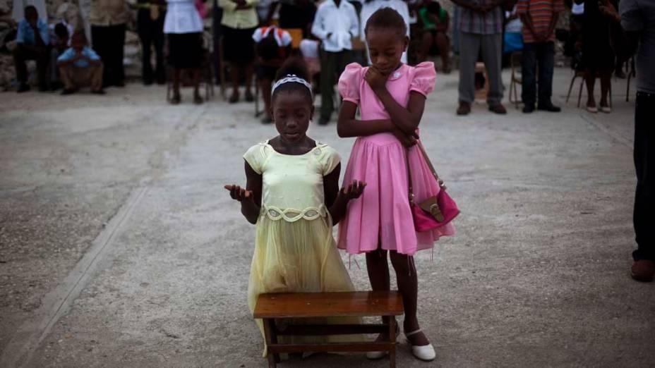 As irmãs Smeralda e Serena rezam nas ruínas da Catedral de Notre Dame, Porto Príncipe, Haiti