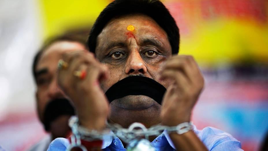 Comerciantes indianos cobrem a boca com roupas pretas e se algemam para protestar contra a recente decisão do governo indiano de abrir grande mercado da Índia varejo para empresas estrangeiras em Nova Délhi