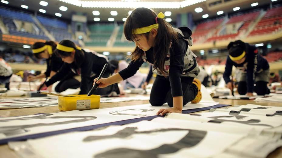 Participantes de todas as idades durante concurso de caligrafia na cidade de Tóquio, Japão