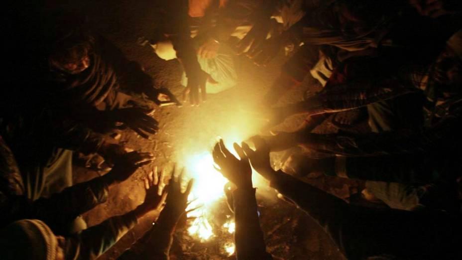 Indianos se juntam ao redor de uma fogueira para se aquecer e se proteger do frio em Amritsar, Índia