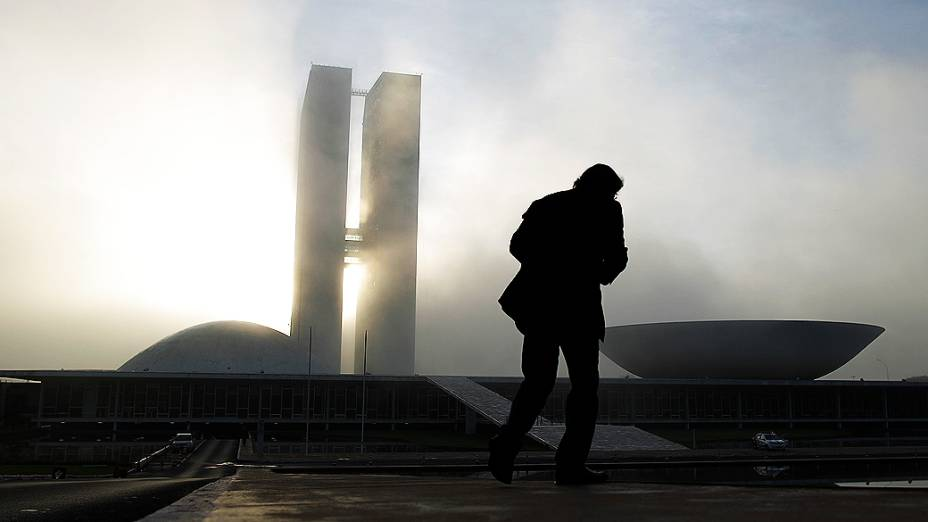 Homem caminha próximo ao Congresso Nacional em Brasília, onde será velado o corpo do arquiteto Niemeyer, nesta quinta-feira