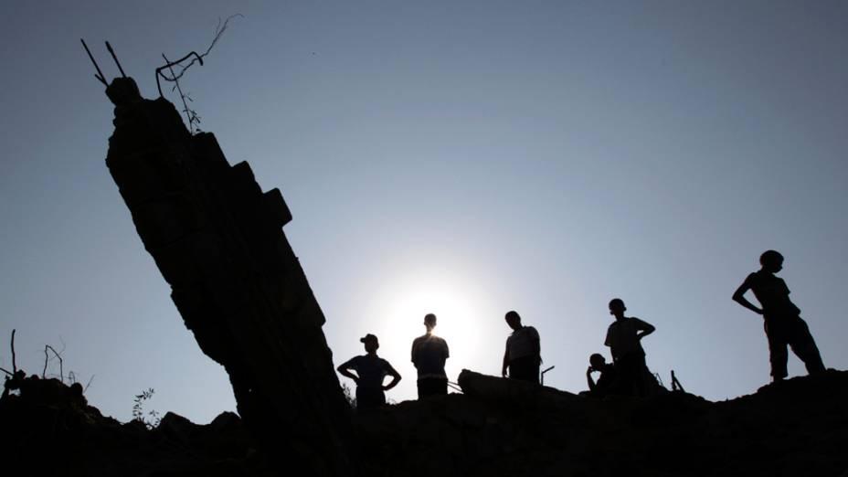 Palestinos inspecionam um edifício depois de ataque aéreo israelense no campo de refugiados de Nuseirat no centro da Gaza Faixa