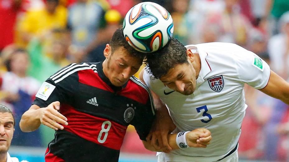 O alemão Ozil disputa de cabeça a bola com o americano Omar Gonzalez na Arena Pernambuco, em Recife