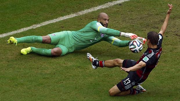 O alemão, Thomas Mueller, desafia goleiro Tim Howard, dos Estados Unido,durante partida em Recife