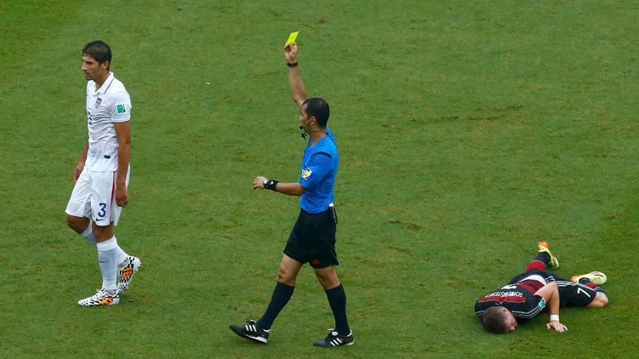 O árbitro, Ravshan Irmatov, do Uzbequistão, mostra o cartão amarelo para Omar Gonzalez, dos Estados Unidos após uma falta sobre Bastian Schweinsteiger, da Alemanha,durante partida na arena Pernambuco, em Recife