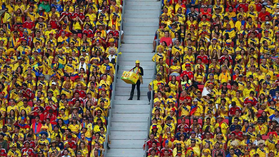 Vendedor passa pela torcida da Colômbia no Estádio Mané Garrincha