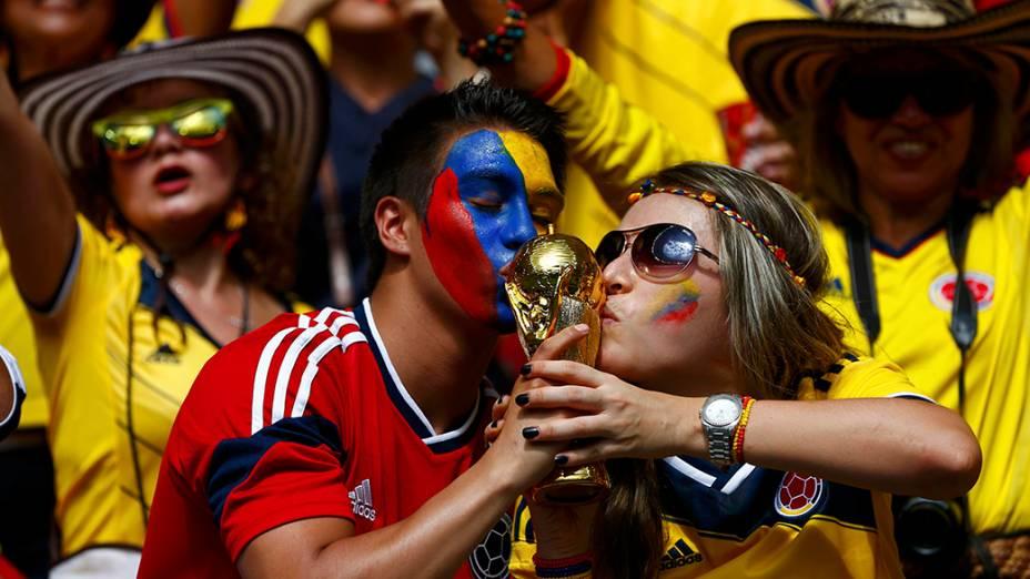Em Brasília, torcedores beijam a taça da Copa do Mundo de Futebol durante uma partida entre Colombia e Costa do Marfim