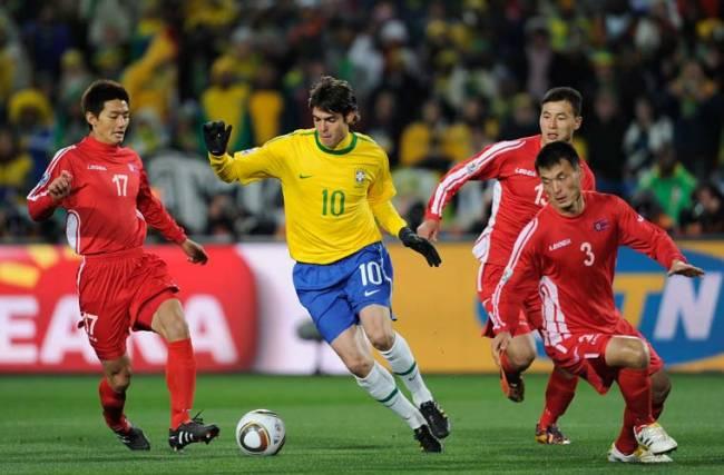 O meia brasileiro Kaká dribla jogadores norte-coreanos.