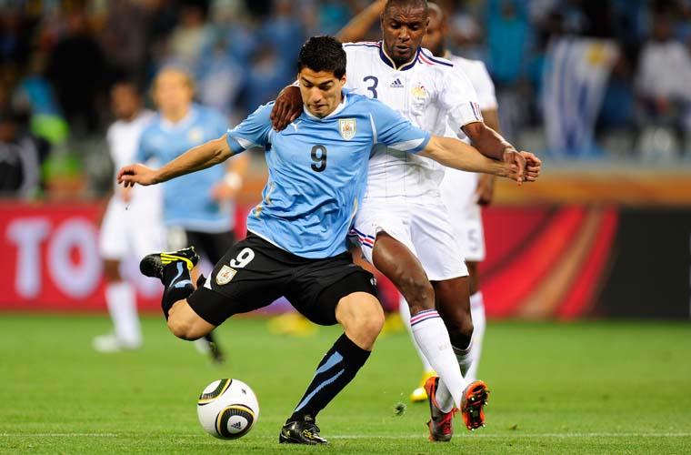 Disputa de bola entre o francês Eric Abidal (direita) e o uruguaio Luis Suarez.