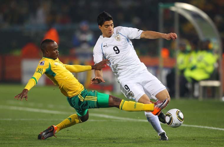 Disputa de bola entre Siboniso Gaxa, da África do Sul e Luis Suarez, do Uruguai.