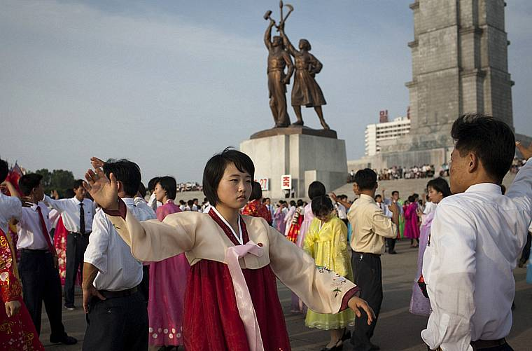 Jovens dançam em frente a torre Juche em Pyongyang