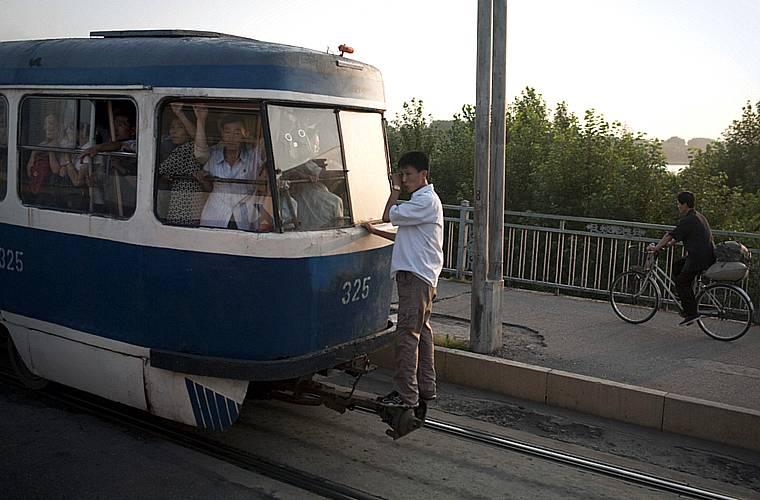 Um surfista coreano, buscando conforto fora do trem, cheio o dia todo.