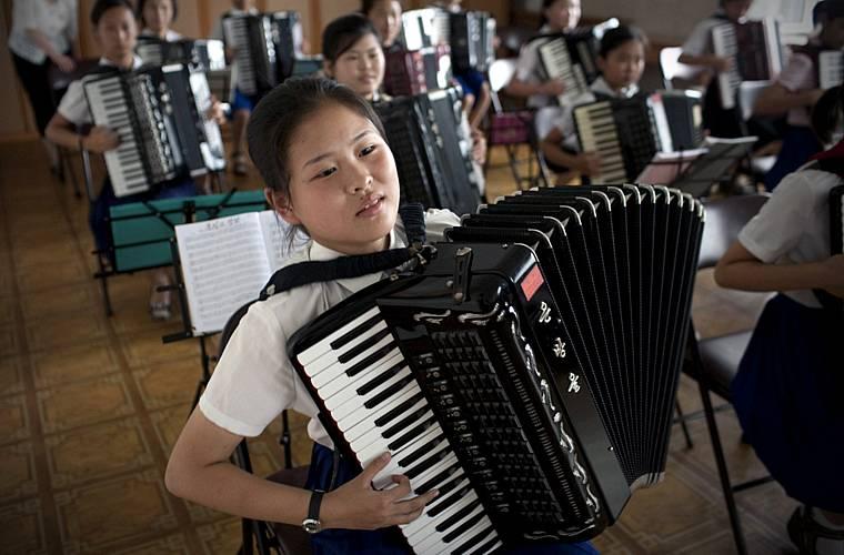 Crianças em aula de acordeão numa escola na capital.