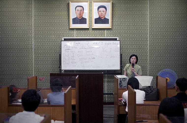 Aula de inglês numa escola de línguas estrangeiras. Na parede, as fotos do presidente Kim Il-sung (à dir.) e Kim Jong-Il