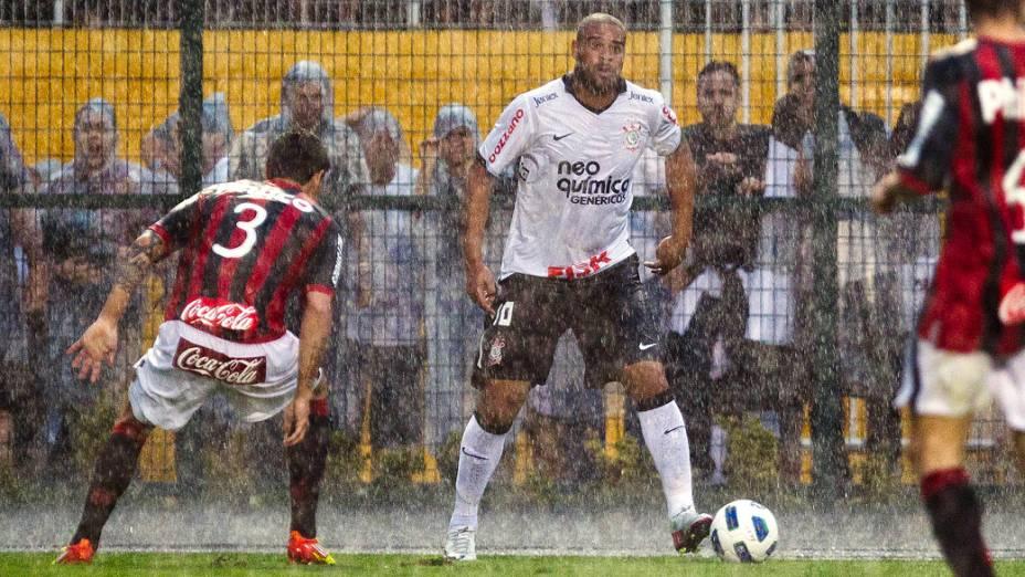 Debaixo de chuva, Fabricio, do Altlético/PR, tenta marcar o corinthiano Adriano, em partida pelo Campeonato Brasileiro - 13/11/2011