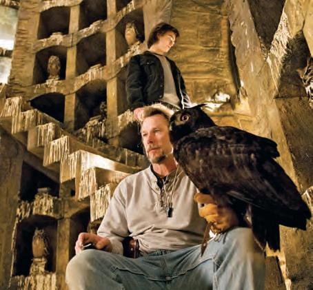 Uma coruja do correio pousada no braço do cuidador David Sousa no cenário do corujal, com Daniel Radcliffe (ao fundo), durante a filmagem de Harry Potter e o Cálice de Fogo (2005).