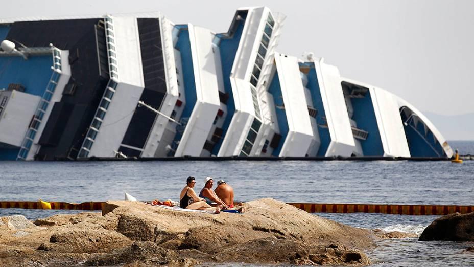 Banhistas aproveitam dia de sol em frente ao navio Costa Concordia, perto do porto de Giglio. A operação para retirar a embarcação da ilha deve começar neste mês