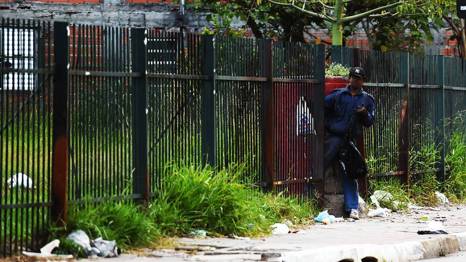 Homem passa entre grades do Piscinão Guaraú, local usado por viciados em crack na Av. Gal. Penha Brasil, em São Paulo