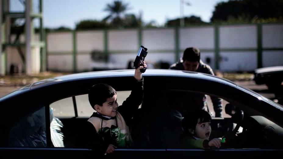 Criança carrega arma de brinquedo perto de quartel destruído em Benghazi, Líbia