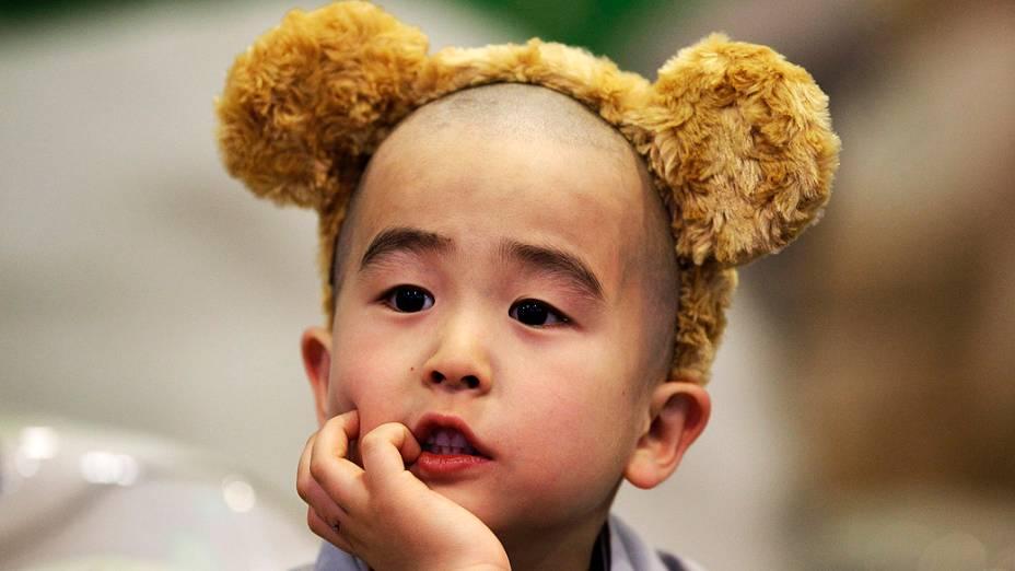 Criança coreana, no parque de diversões Everland em Yongin, a oeste de Seul; crianças frequentam o templo para ter uma experiência de vida de monge e para comemorar o aniversário próximo de Buda daqui a três semanas