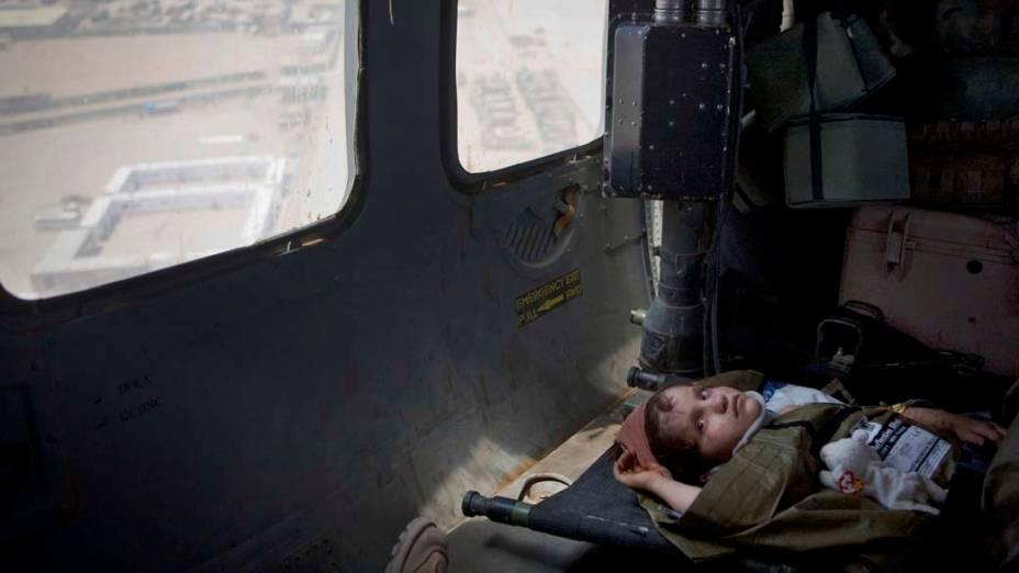 Criança afegã a caminho de um hospital militar em Helmand, Afeganistão. A menina sofreu ferimentos na cabeça após cair de um caminhão e foi socorrida pelos militares americanos