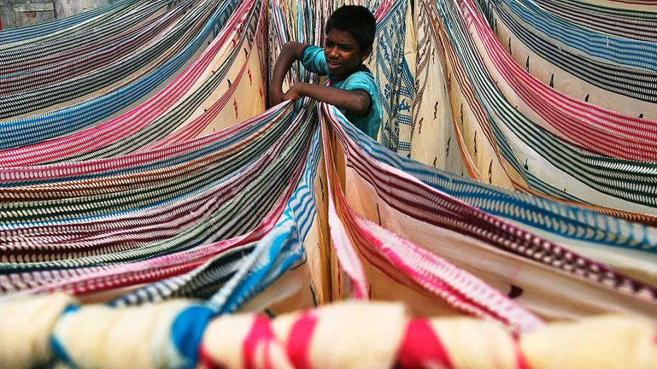 Um menino separa tecidos deixados para secar no telhado de uma fábrica de algodão em Hyderabad, na Índia