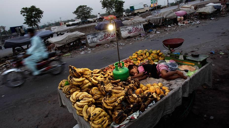 Menino de 2 anos, dorme em meio às mercadorias do pai à beira de uma rua perto de Islamabad, no Paquistão