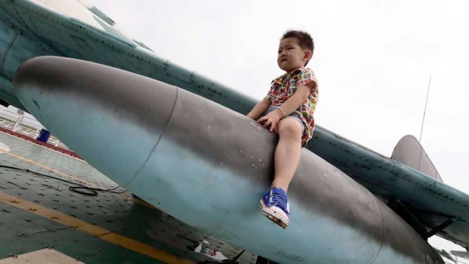 Garoto sobre míssil da antiga União Soviética na praia Bagua, em Tianjin, China