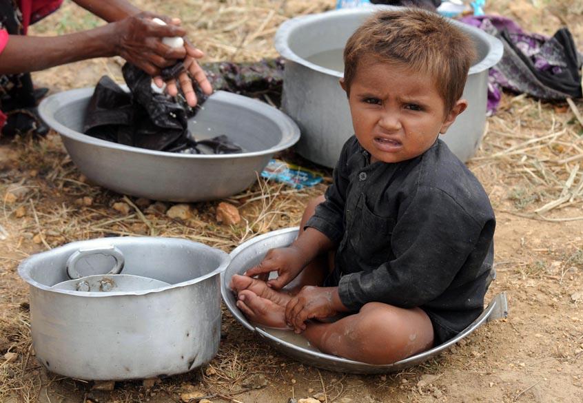 Criança paquistanesa fica ao lado de sua mãe enquanto ela lava roupas em um abrigo improvisado. Mais de 300.000 paquistaneses deixaram suas casas por conta das inundações. Veja galeria de fotos sobre as enchentes no Paquistão