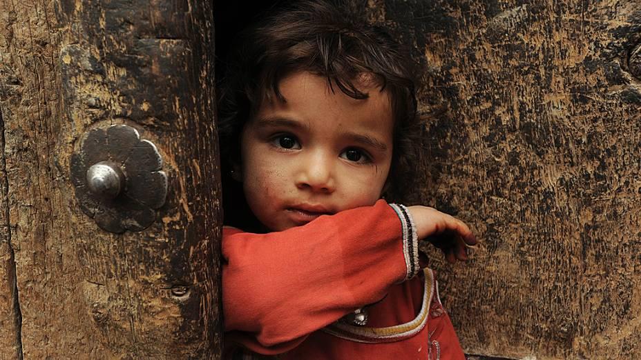 Menina afegã olha para fora da porta de sua casa na parte velha de Cabul