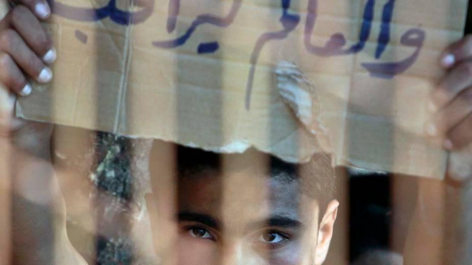 """Garoto sírio carrega cartaz com a frase """"Nós estamos morrendo e o mundo está assistindo"""", durante protesto em um campo para refugiados na cidade de Yayladagi, Turquia"""