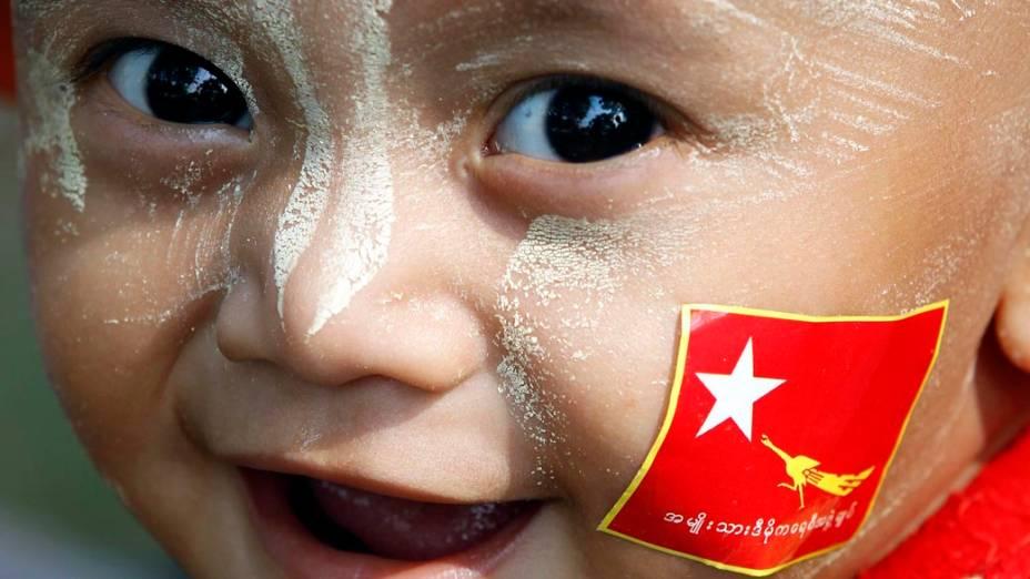 Criança com a bandeira da Liga da Oposição Nacional para a Democracia (NLD), durante campanha eleitoral em Mianmar